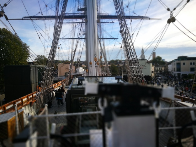 arty photo of the ship's rigging with the town of greenwich in the background