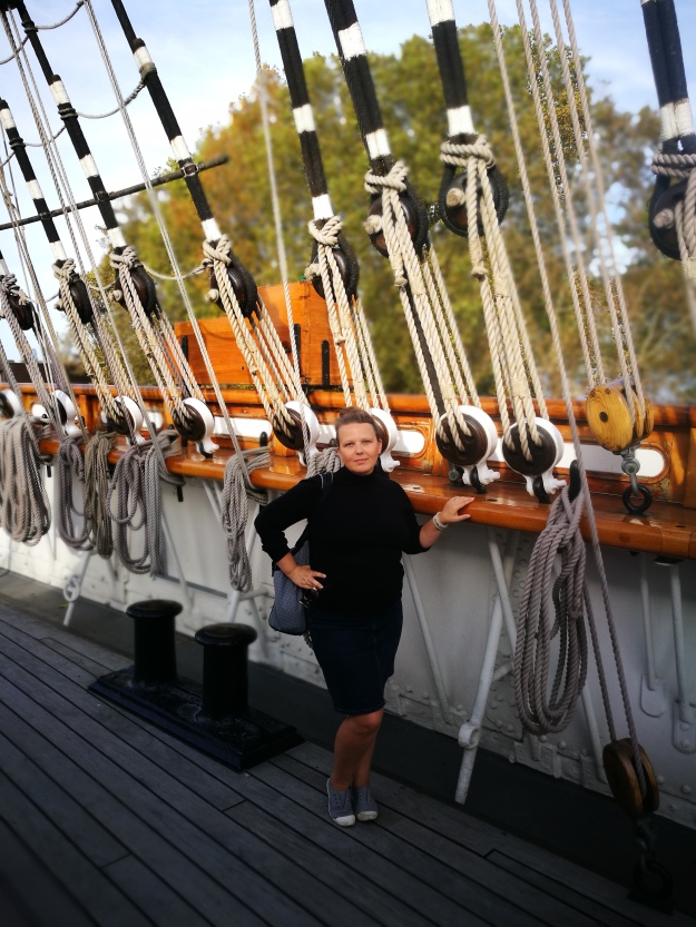 photo of me in a black turtleneck and denim skirt and canvas slip on shoes on the deck of the cutty sark in front of the rigging and pulleys