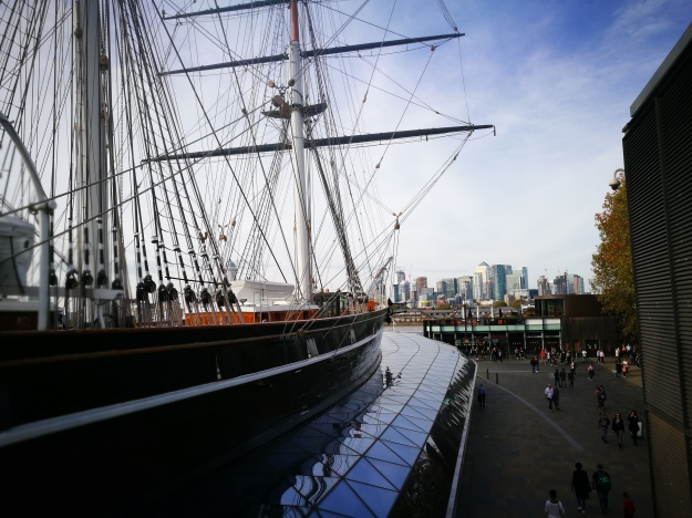 A side view of the Cutty Sark tea clipper in Greenwich. There is a view of the towers of Canary Wharf in the background.