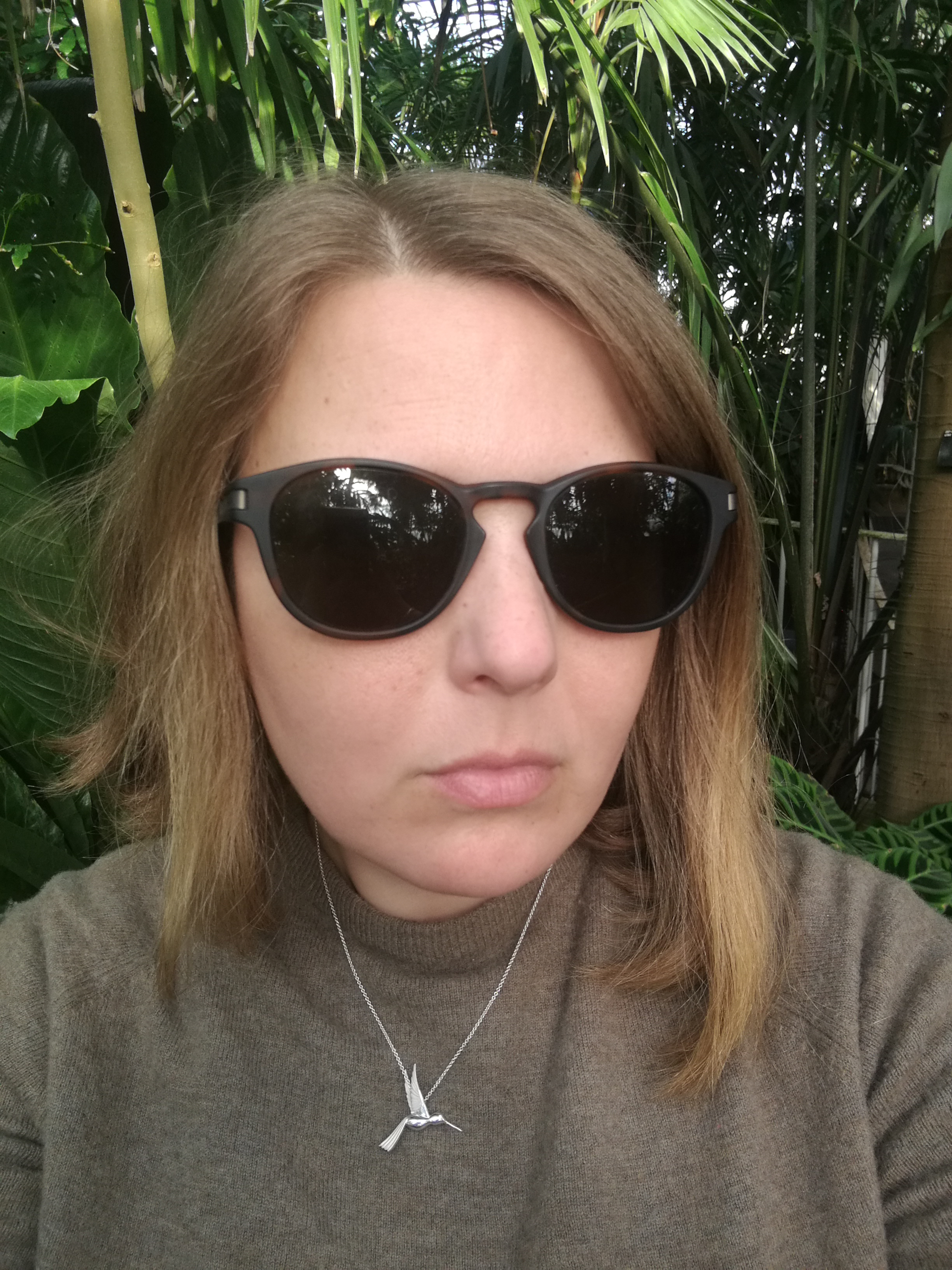 Photo of me wearing Oakley sunglasses, a thrifted J Crew jumper in a mossy brown and wearing the silver hummingbird pendant. My hair's a bit frizzy!