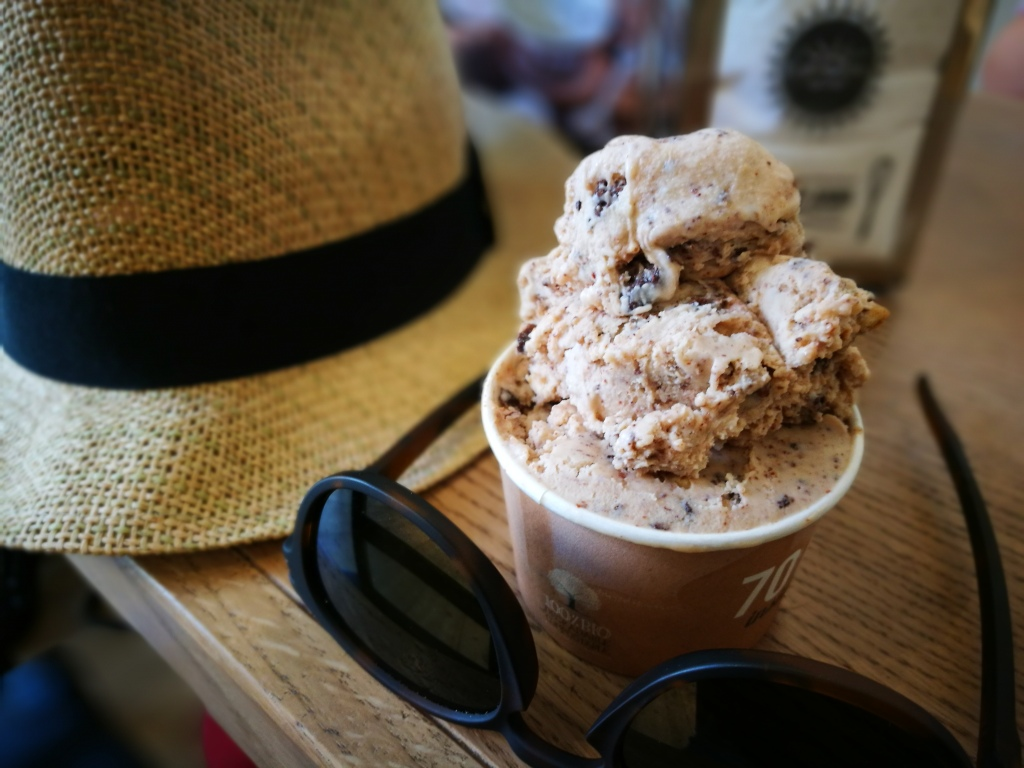 A photo of a tub of vegan ice cream beside my rattan sunhat and oakley sunglasses.  On a cafe table.