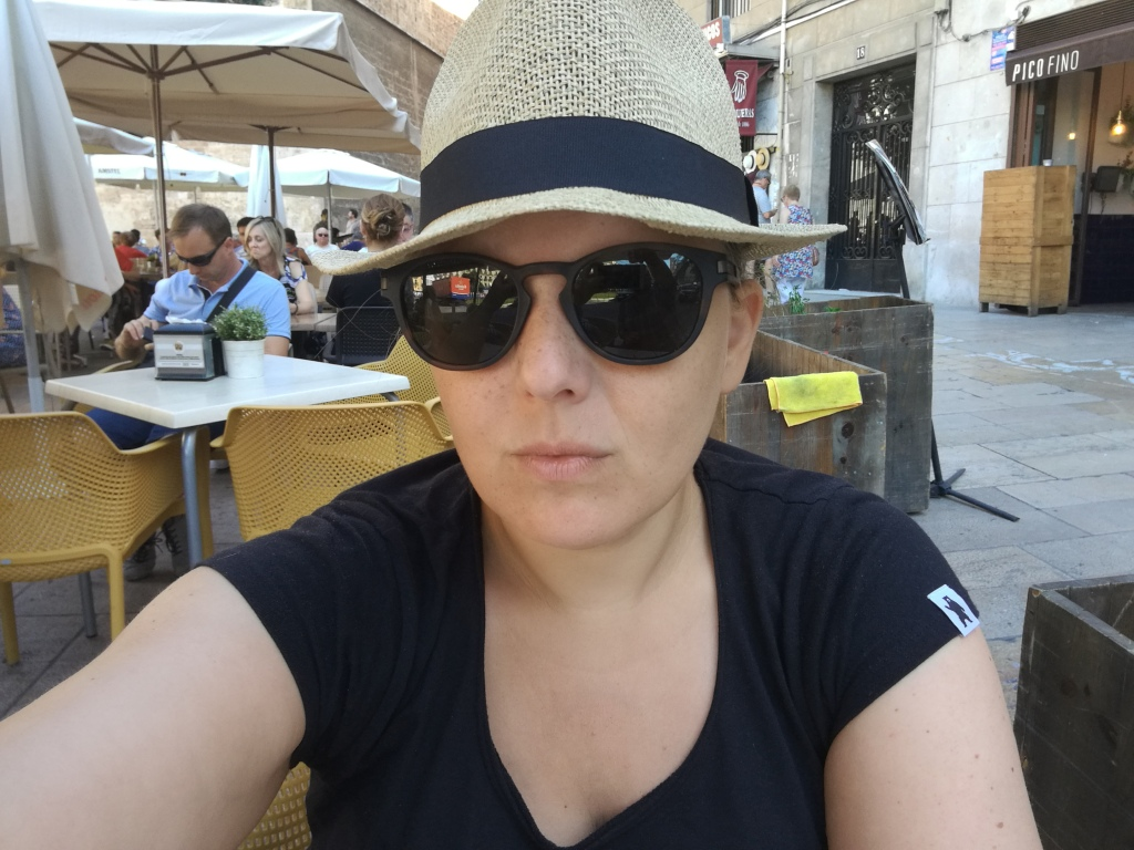 Me wearing a black t shirt and sunglasses and a sunhat at a cafe table in Valencia.
