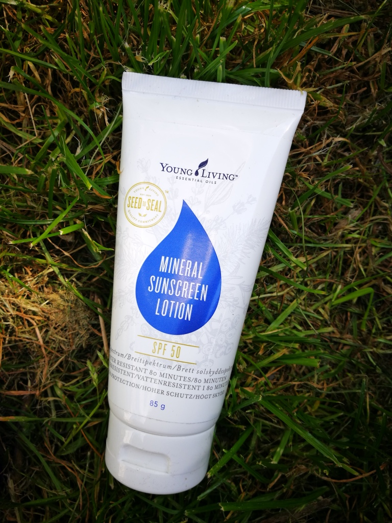 Young Living brand SPF 50 sun lotion on the grass.